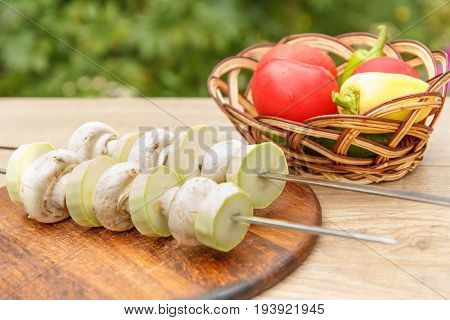 Zucchini And Mushrooms On Metal Skewers On Wooden Chopping Board With Tomatoes,  Cucumber And Bell P