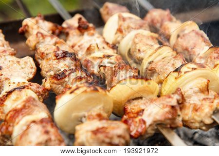 Meat And Onions On Skewers Are Grilling On Charcoal