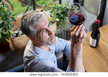 A glass of red wine for dinner. Man drinking wine