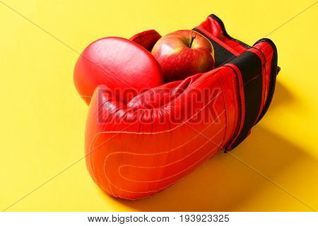 Sport equipment and fruit on sunny yellow background. Knock out and healthy nutrition concept. Pair of leather boxing sportswear with juicy red apple. Boxing gloves in red color