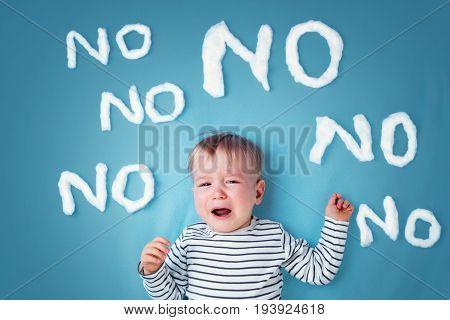 sad boy on blue blanket background. Unhappy child with no words around