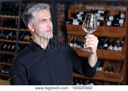 A shot without streaks. Man watches a crystal wine glass.