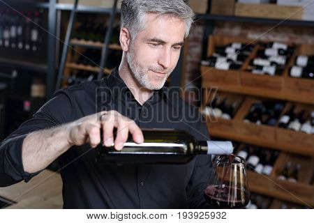 Man poured red wine into a glass.