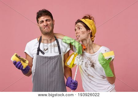 Tired Housewife With Dirty Face And T-shirt Holding Washing Spray And Sponge Leaning At Shoulder Of