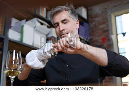 The waiter polishes the glass.A handsome bartender polishes a glass of wine glasses.