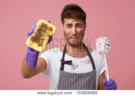 Indoor Portrait Of Unhappy Crying Young Bearded Man In Apron And Rubber Gloves Feeling Sad And Upset
