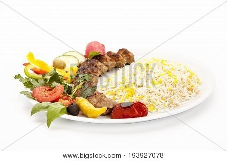 Low angle view of a grilled lamb kebab kubide served with rice pepper tomato and herb on a simple plate. Well roasted ground meat balls taken off the skewer. Studio shot over white background.