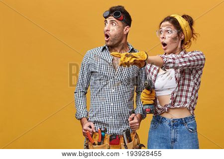 Two Astonished Electricians With Dirty Faces Looking Sideways In Shock: Woman In Protective Gloves A
