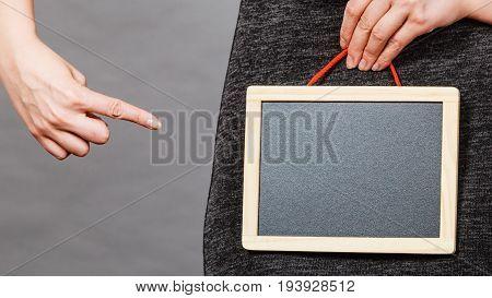 Feminine body problems concept. Woman holding blank black board on crotch grey background.