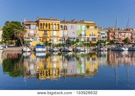 VALENCIA, SPAIN - JUNE 13, 2017: Colorful houses with reflection in the water of Port Saplaya in Valencia, Spain