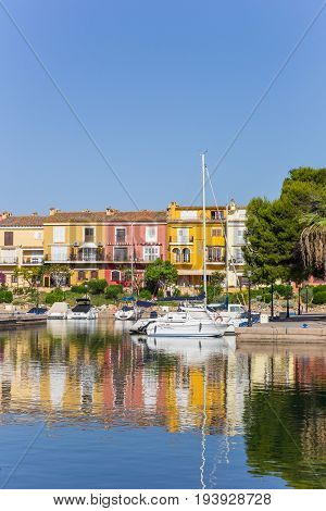 VALENCIA, SPAIN - JUNE 13, 2017: White sailing ship and colorful houses in Port Saplaya, Valencia, Spain