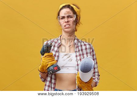 Young Pretty Female Worker Wearing Protective Eyewear, Gloves And Casual Shirt Holding Drilling Mach