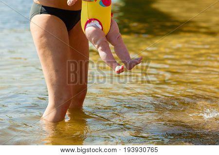 Litte cute baby feet in stroller in sunlight