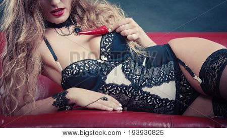 Sensual seductive attractive woman wearing lingerie holding chilli pepper. Erotic fashion concept half face