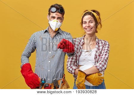 Horizontal Portrait Of Young Foreman Wearing Safety Eyewear, Mask And Red Gloves Holding Tool Belt P