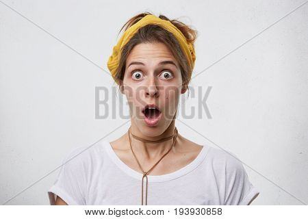 Indoor Shot Of Pretty Woman Looking With Bugged Eyes And Jaw Dropped Wearing Yellow Scarf On Head, P