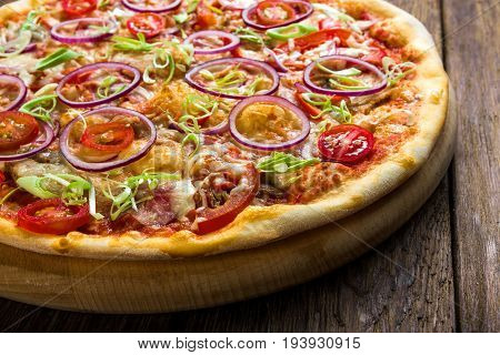 Delicious pizza on wood, with onions, bacon and cherry tomatoes, thin pastry crust, closeup