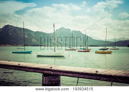 Small sailboats anchoring in alpine lake. Landing stage and mountains framing the boats. Bavaria, Germany, Allgau, Forggensee. Retro vintage style.
