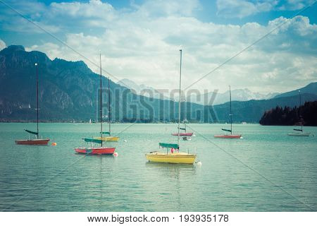 Small colorful sailboats anchoring in turquois alpine lake in front of mountains. Bavaria, Germany, Allgau, Forggensee. Retro vintage style.