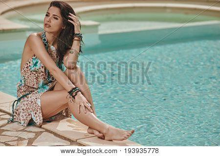 Beautiful woman in Elegant dress. Sexy brunette lying by blue swimming pool. Fashion outdoor portrait. Luxury resort.