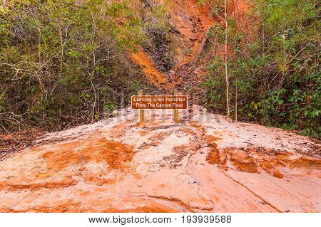 The prohibit sign standing on the red loamy floor of Providence Canyon USA