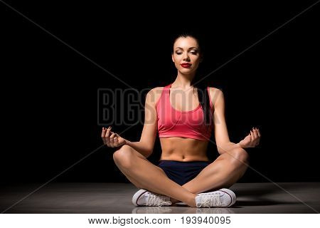 Portrait of happy sporty woman relaxing in lotus position. Joyful female model breathing fresh air indoors. Healthy active lifestyle and yoga concept