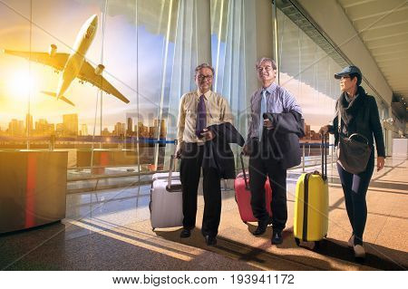 two business man and woman with traveling luggage walking in airport teminal