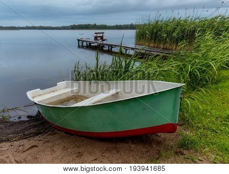 Fisherman's boat on the beach during rain in the evening on Masuria Poland. In background bridge with fisherman poles