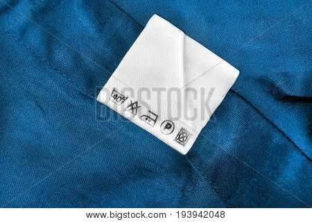 Washing instructions white clothes label on blue cotton as a background