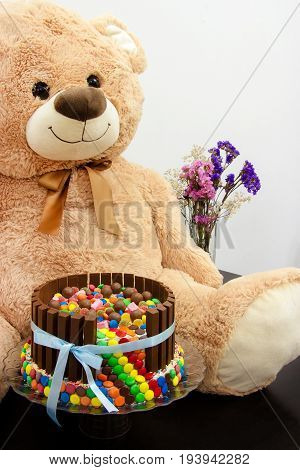 Happy birthday cake and big Teddy Bear. Festive tea party. Pinata Cake a celebration cake with a hidden stash of sweets inside.