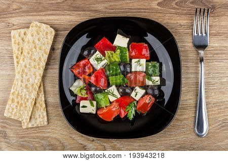 Greek Salad In Black Plate, Crispbread And Fork On Table