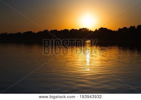 Sunset sky above the forest lake. Afterglow nature background
