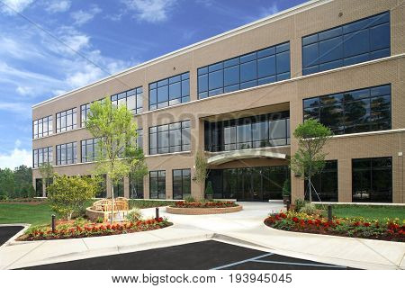 Generic Brick Office Building Exterior with lush Landscaping trees and flowers