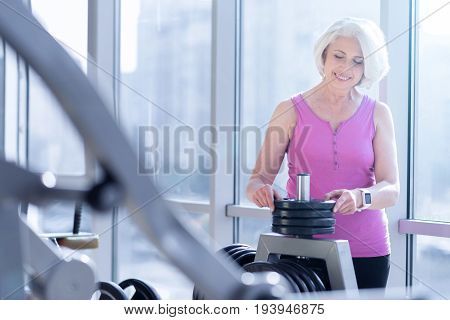 Choosing weight. Pretty senior woman is standing at window in gym and choosing dumbbell for exercising.