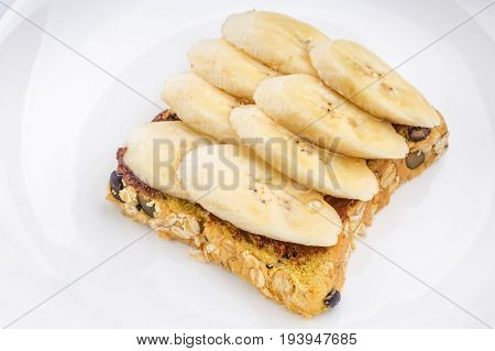 Chocolate and sliced banana on open wholewheat sandwich bread topped with honey served in white plate healthy eating concept.
