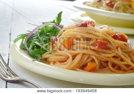 Spaghetti marinara pasta salad with arugula on table