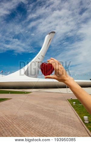 June 18, 2017, Sochi, Russia. The Girl Is Holding A Heart In Front Of The Torch Of The Olympic Flame