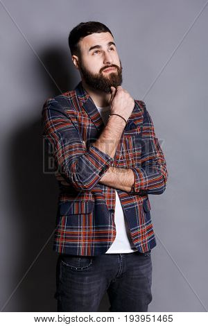 Pensive young bearded hipster looking upwards. Handsome relaxed guy in checkered jacket dreaming about something, lost in thoughts, gray studio background