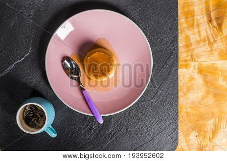 Flan - A Sweet Custard Creme Caramel With Creme On Top, On A Pink Plate Over A Wooden Board.