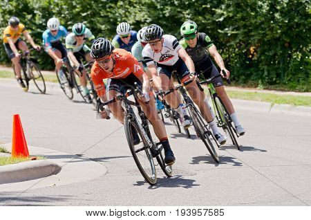 STILLWATER, MINNESOTA - JUNE 18, 2017: Cyclists in peloton turn corner at the 2017 North Star Grand Prix Men's Stillwater Criterium. It is the final stage of a six-stage annual race.