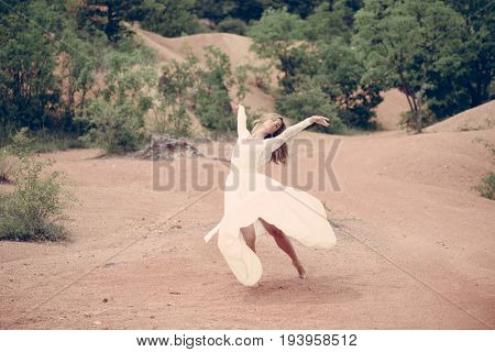 Carefree bride doing dance moves outdoors. Happy bride dancing.