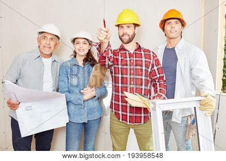 Group of craftsmen as team working and planning building construction