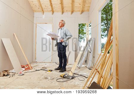 Senior as architect and master craftsman during house renovation
