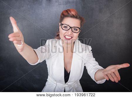Annoyed Teacher Stretch Hands On Chalkboard Background