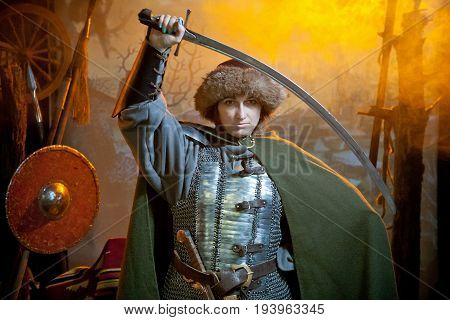 A woman dressed in chain mail cloak and fur hat with a scimitar in her hands against the background of weapons and a castle in the distance