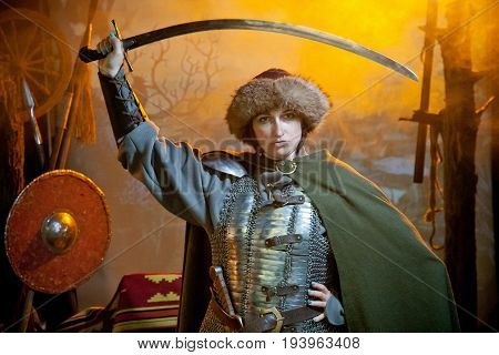 A woman dressed in chain mail cloak and fur hat with a scimitar in her hands against the background of weapons a branch with a crow and a castle in the distance