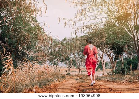 Alone young girl walking on the dirt road in  landscape and life isn't a bed of roses concept