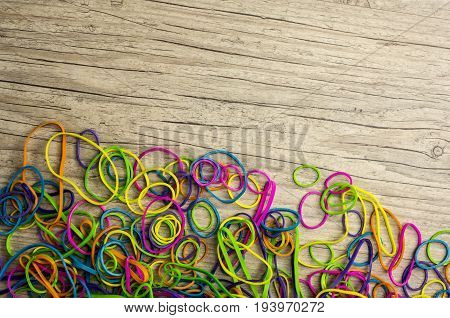 Close up shot of vibrant colored rubber bands on wood background