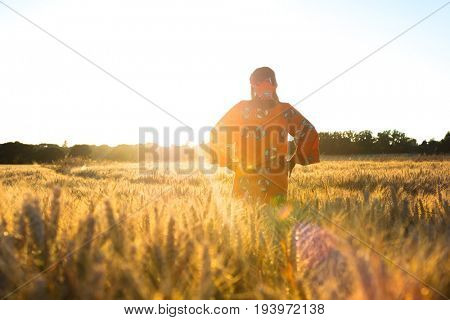 African woman in traditional clothes standing in a field of barley or wheat crops at sunset or sunrise