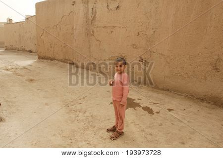 Khiva Uzbekistan - March 08 2009: Poverty in Uzbekistan. The boy is in pajamas and sandals that are large.